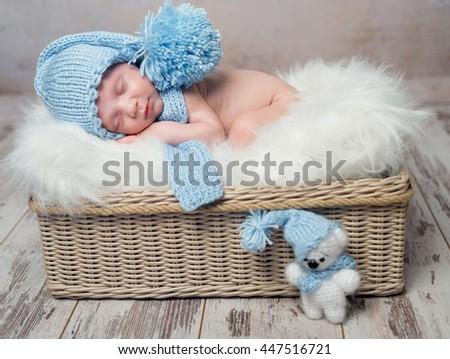 baby in blue hat sleeping on fluffy blanket in wicker basket - stock photo