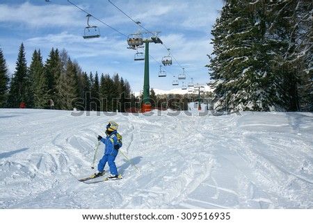 Baby in blue overalls ski on a ski slope under the seat. Cabs for skiers above. Val di Fiemme, Italy. - stock photo