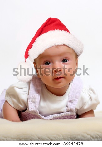 Baby in Christmas bonnet looks at camera, on white background - stock photo