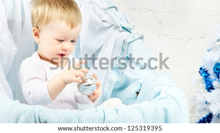 baby in cradle playing with christmas ball - stock photo