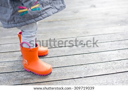 Baby in cute bright orange rubber boots on wood background