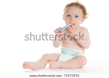 baby in diaper brushing teeth on white ground - stock photo