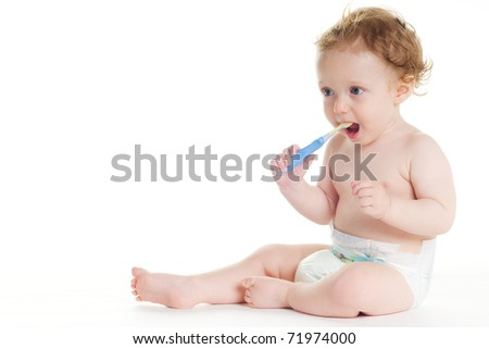 baby in diaper brushing teeth on white ground