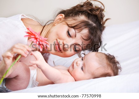 Baby in diaper playing with pink flower - stock photo