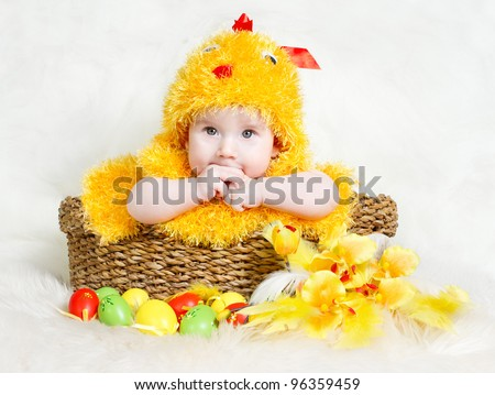Baby in Easter basket with eggs in chicken costume. Easter holiday concept: nest with baby chick - stock photo