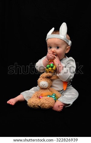 Baby in easter clothes with chocolate eggs - stock photo
