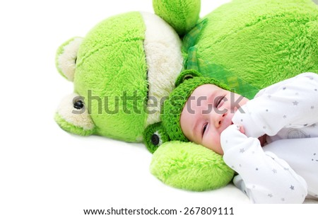 baby in frog hat and soft toy - stock photo