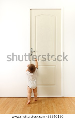 Baby in front of a closed door, trying to reach the keyhole with key - stock photo