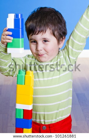 Baby in green shirt playing with bright blocks looking up in surprise