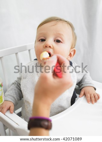 Baby in high chair being fed by adult. Vertically framed shot.