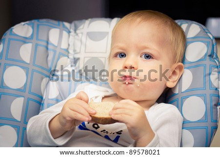 Baby in high chair eating bread - stock photo