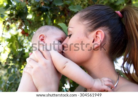 Baby in his mother's arms. Closeup of a mother playing with her naked baby in diaper. The language of the eyes of a baby. - stock photo