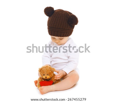 Baby in knitted brown hat with teddy bear toy - stock photo