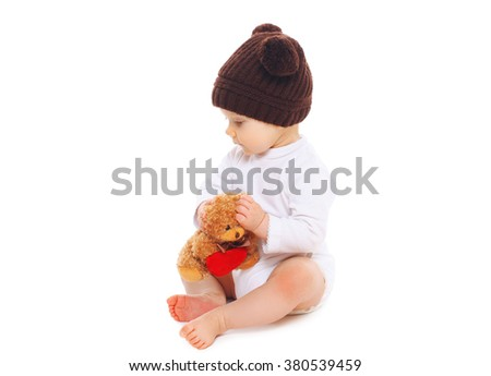 Baby in knitted brown hat with teddy bear toy sitting on white background - stock photo