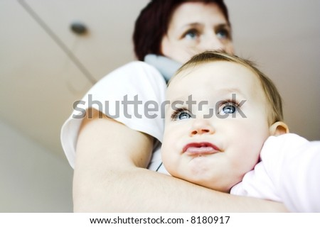 Baby  in mother´s arms - making funny faces - stock photo