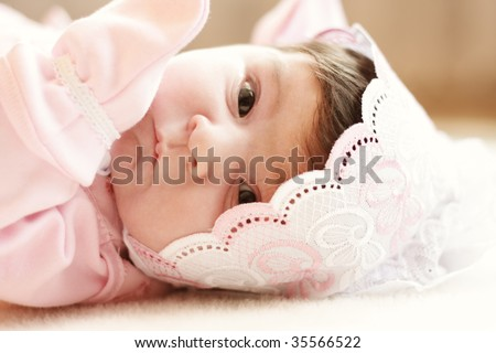 Baby in pink clothes laying down on blanket