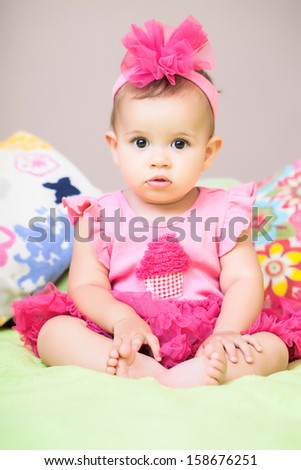 Baby in pink sitting on the sofa