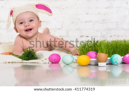 Baby in rabbit costume smiles  and plays easter eggs. Fresh grass - stock photo