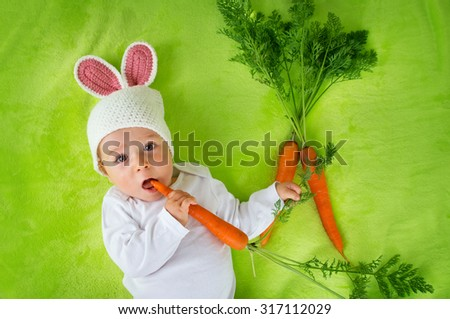 Baby in rabbit hat eating fresh carrot - stock photo