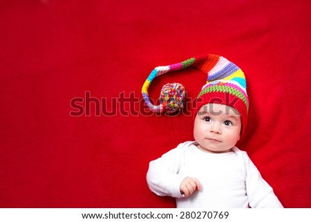 Baby in red and white hat on the bed - stock photo