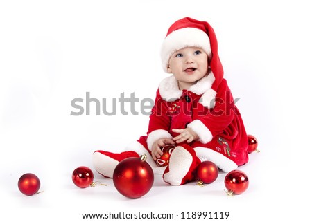 Baby in red costume playing with Christmas decoration - stock photo