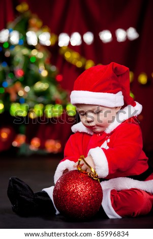 Baby in Santa clothing busy playing with large Christmas ball - stock photo