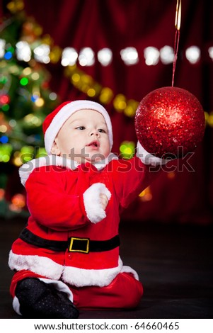 Baby in Santa costume playing with huge Christmas ball - stock photo