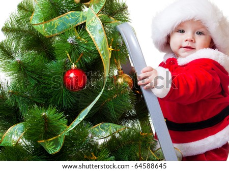 Baby in Santa costume standing on a step ladder and decorating Christmas tree - stock photo