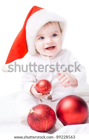 Baby in Santa hat playing with Christmas ball