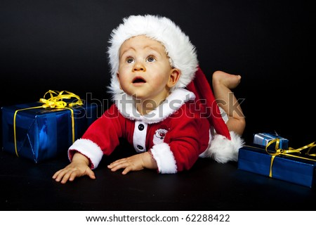 Baby in Santa hat playing with Christmas box, isolated - stock photo