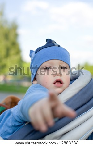 Baby in sitting stroller pointing his finger right at you - stock photo