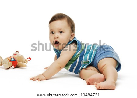 Baby in striped blue shirt on the floor against white background - stock photo