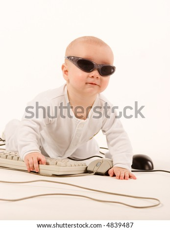 Baby in sun glasses playing with computer - stock photo