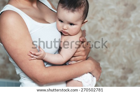 baby in the arms of his mother - stock photo