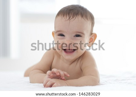 Baby in the bed looking at camera and smile - stock photo