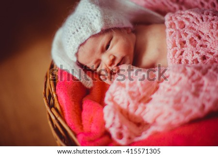 Baby in the funny white hat in the basket - stock photo