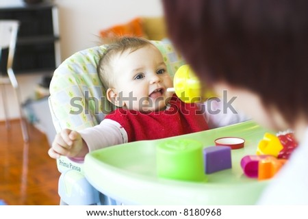 Baby in toddler seat - drinking - stock photo