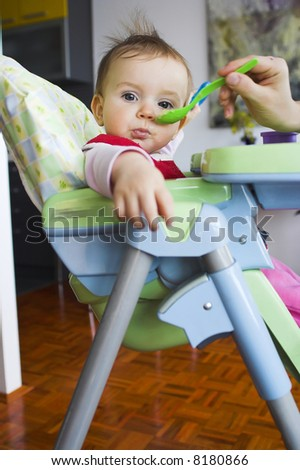 Baby in toddler seat - eating - stock photo