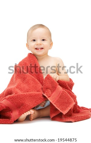 baby in towel sitting on the floor - stock photo