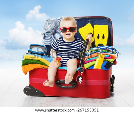 Baby in Travel Suitcase. Kid inside Luggage Packed for Vacation Full of Clothes, Child and Family Trip - stock photo