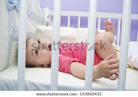 Baby in white cradle with big black eyes. - stock photo