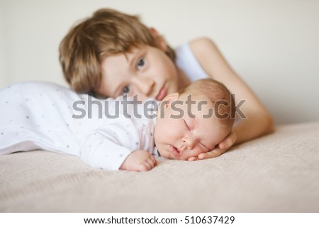 baby in white pajamas sleeping on his stomach,  older brother hugs