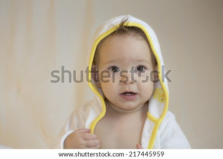 Baby in yellow and white bathrobe looking at camera.