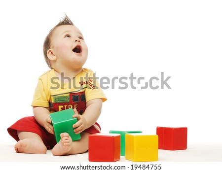 Baby in yellow shirt playing with bright blocks looking up in surprise - stock photo