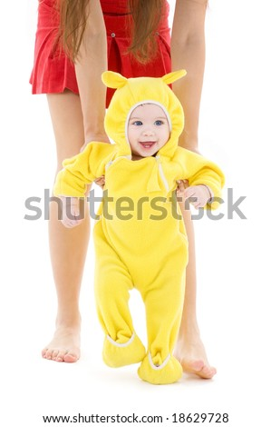 baby in yellow suit making first steps - stock photo