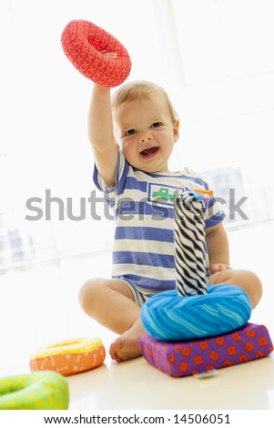 Baby indoors playing with soft toy - stock photo