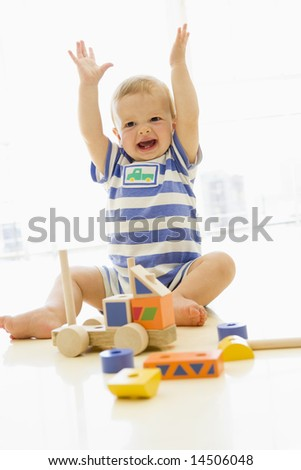 Baby indoors playing with truck - stock photo