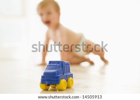 Baby indoors with toy truck - stock photo
