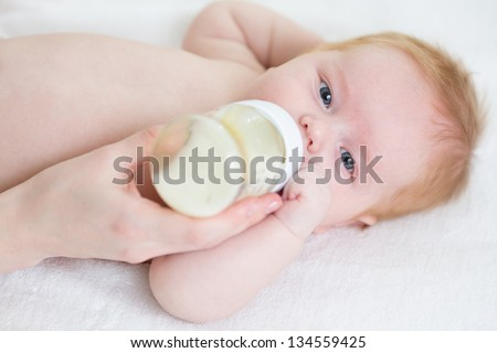 baby infant eating milk from bottle - stock photo