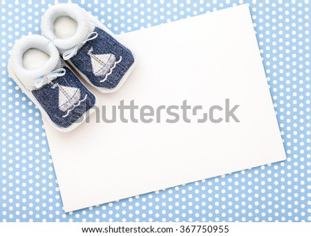 Baby invitation card with baby blue shoes and blue polka dot background. - stock photo